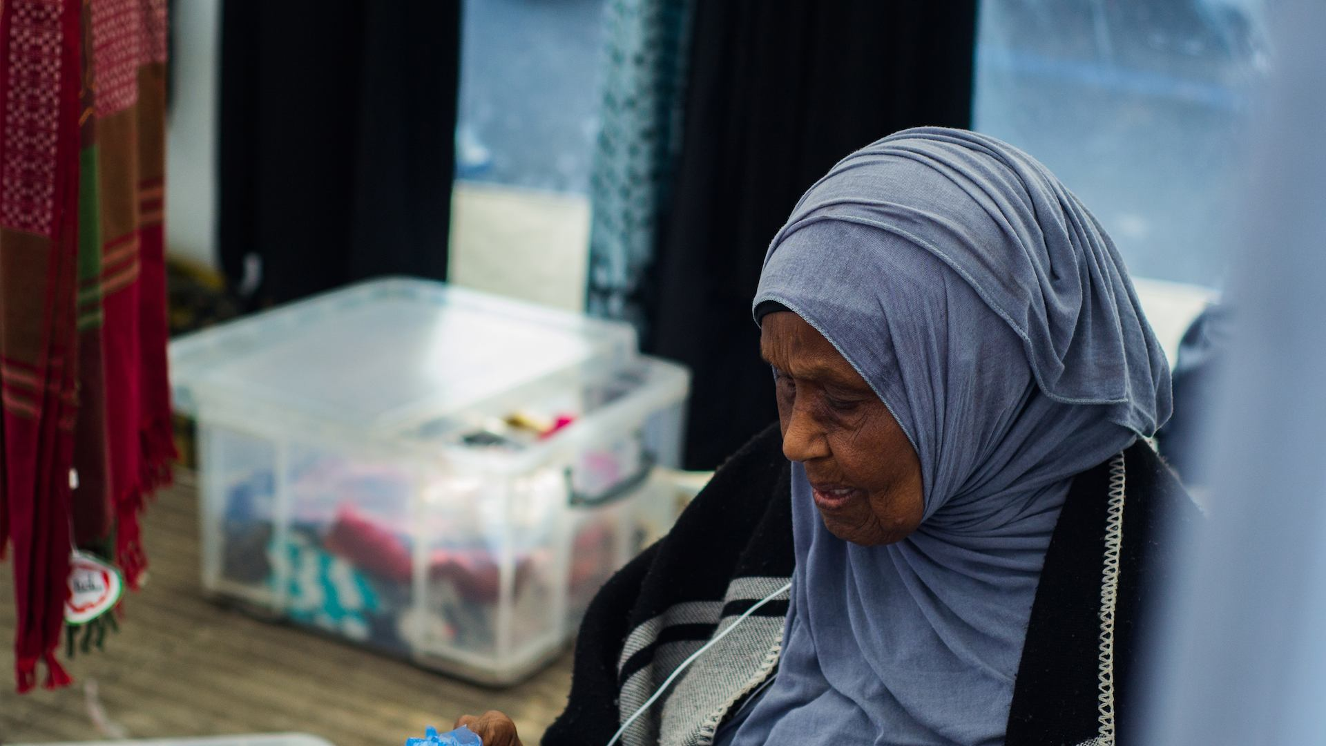 Older lady in hijab by stall in East Street Market
