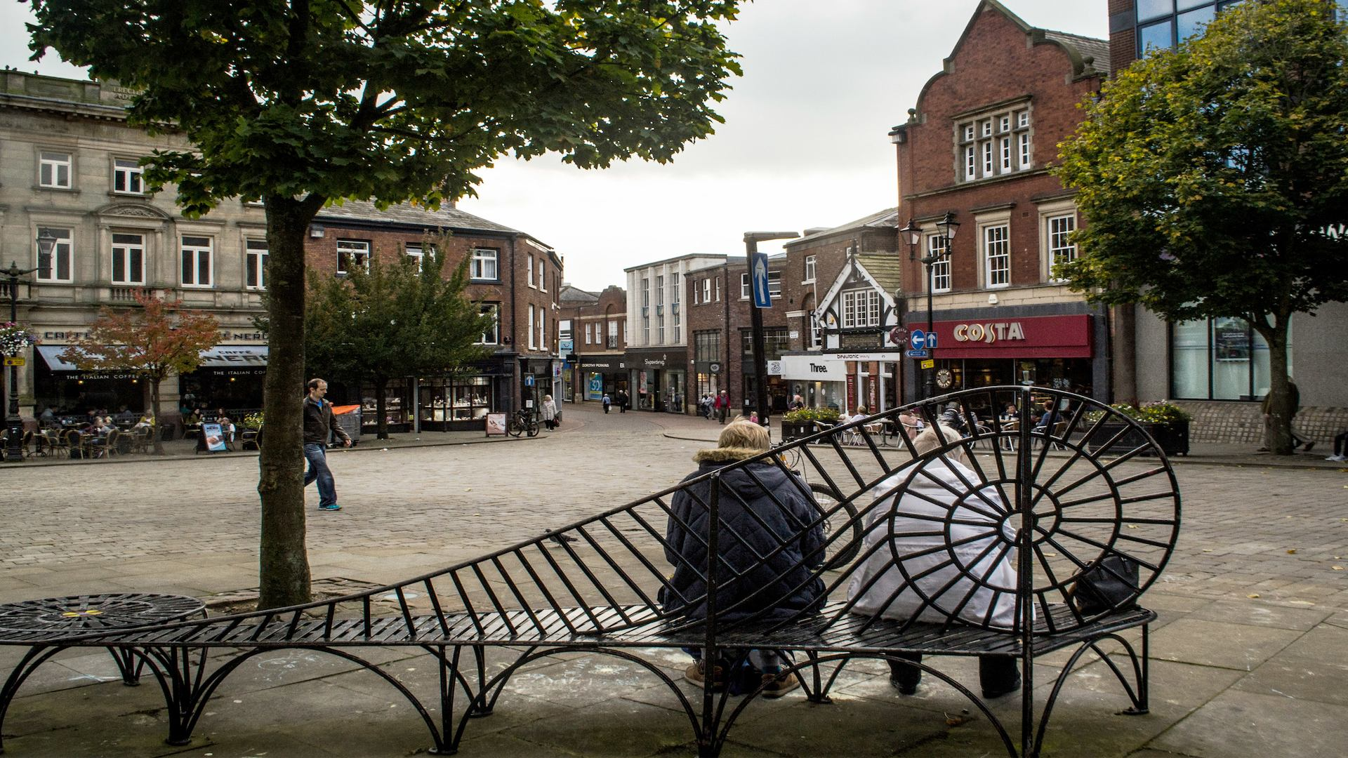Two women sitting on a bench in Macclesfield