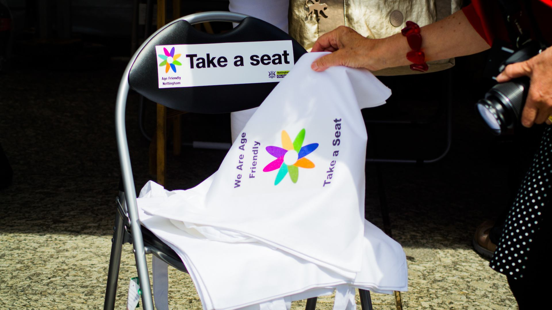 Chair with Take a seat campaign sticker and Take a seat campaign tote bags.