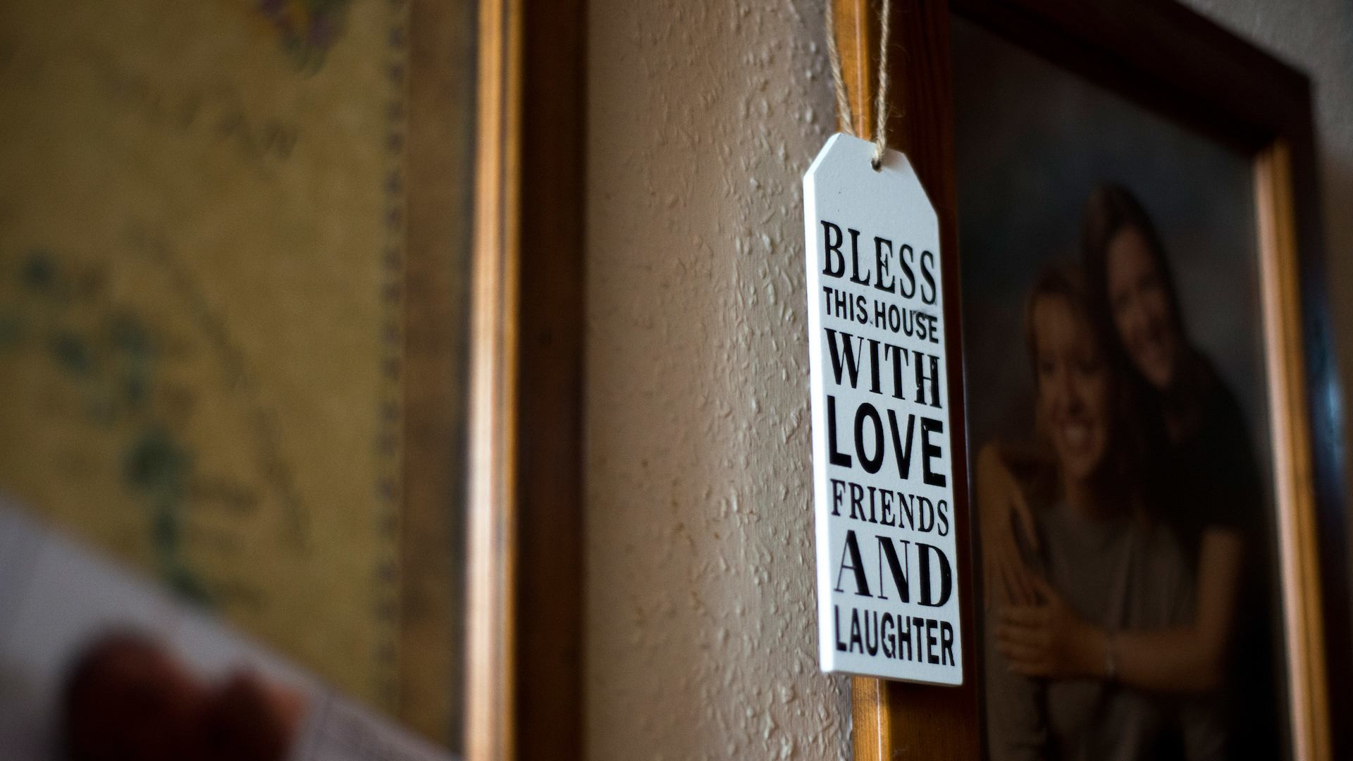 'Bless this house with love, friends and laughter' tag hanging from a family photo.