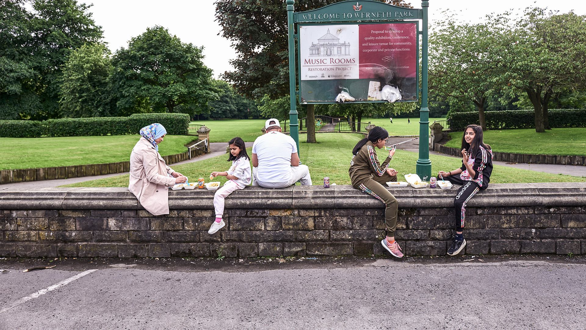 Family group sitting on a wall in a park