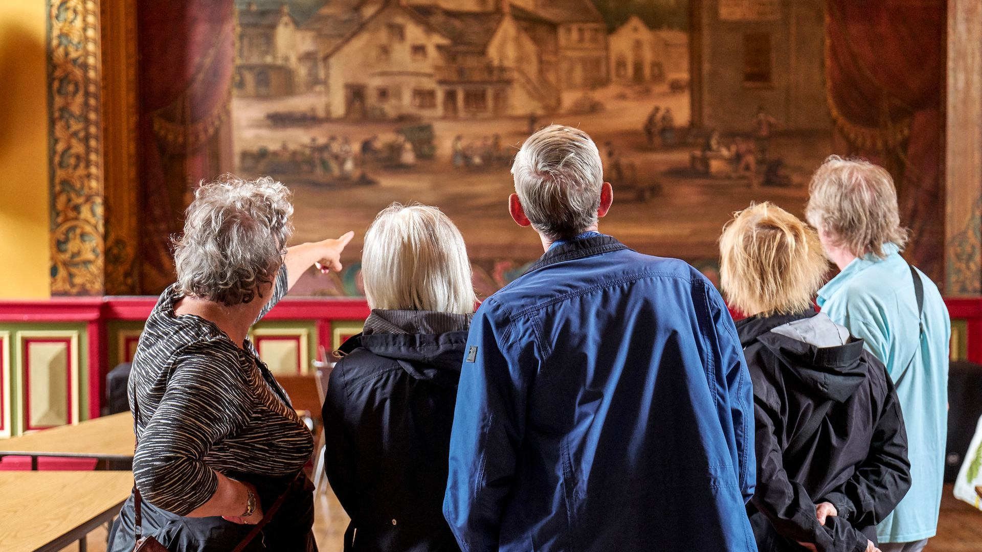 Group of elderly people in a museum looking at a work.