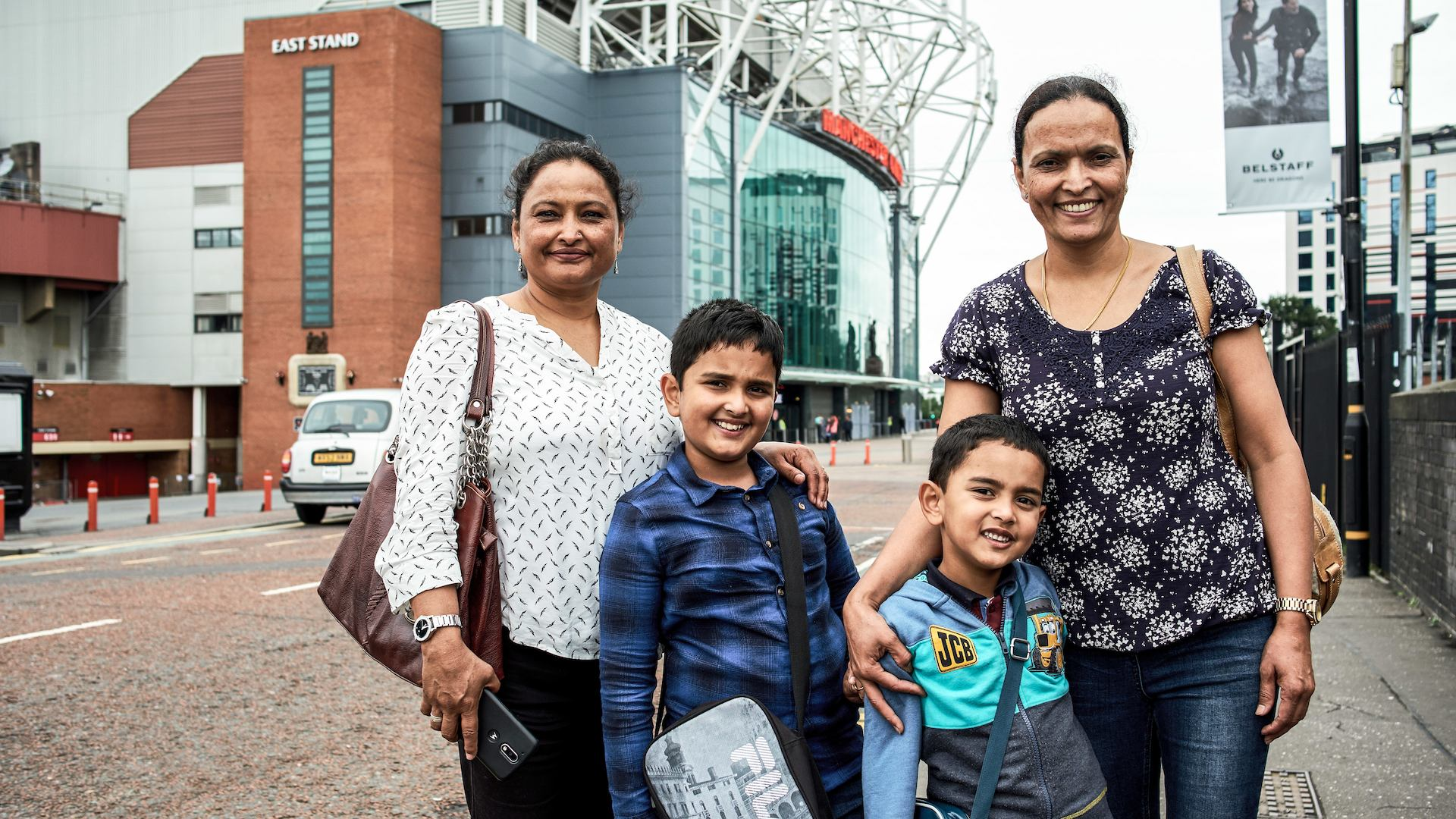 Asian British family smiling at the camera outside Old Trafford