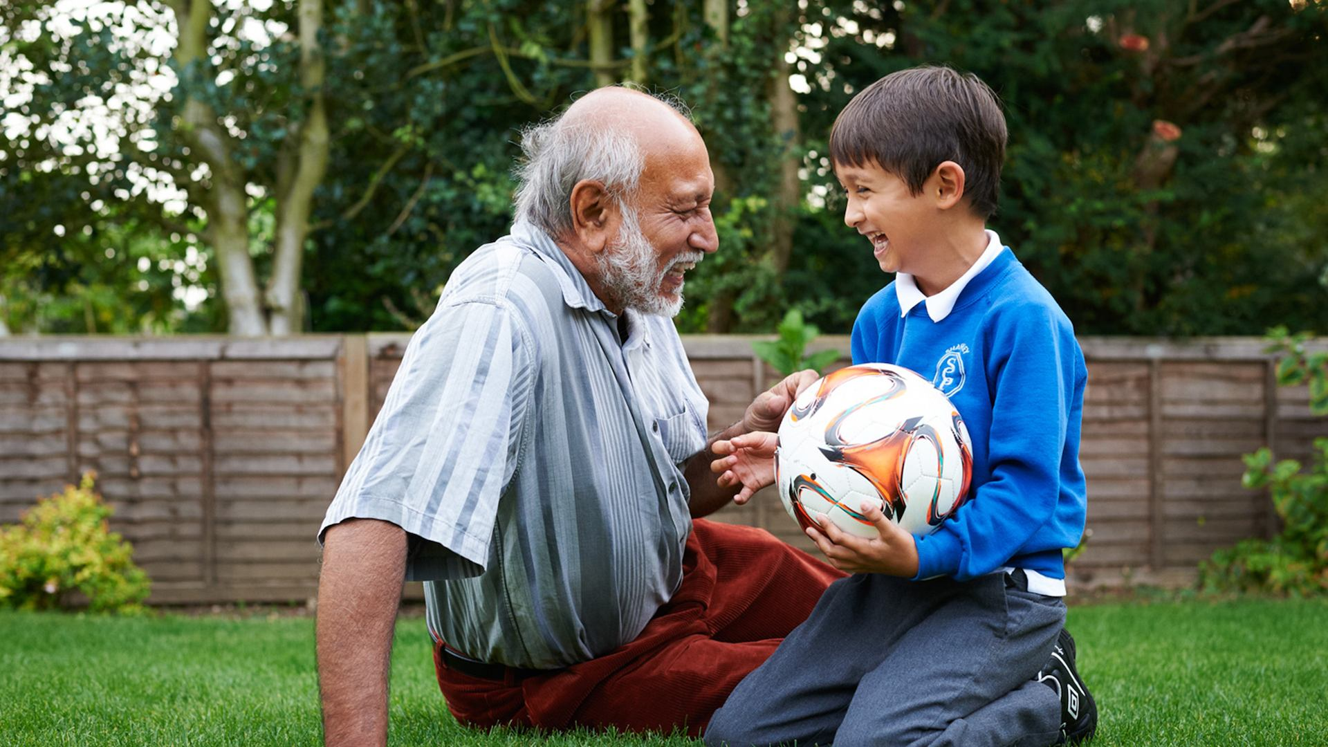 Elderly man and grandson sitting on grass with football.