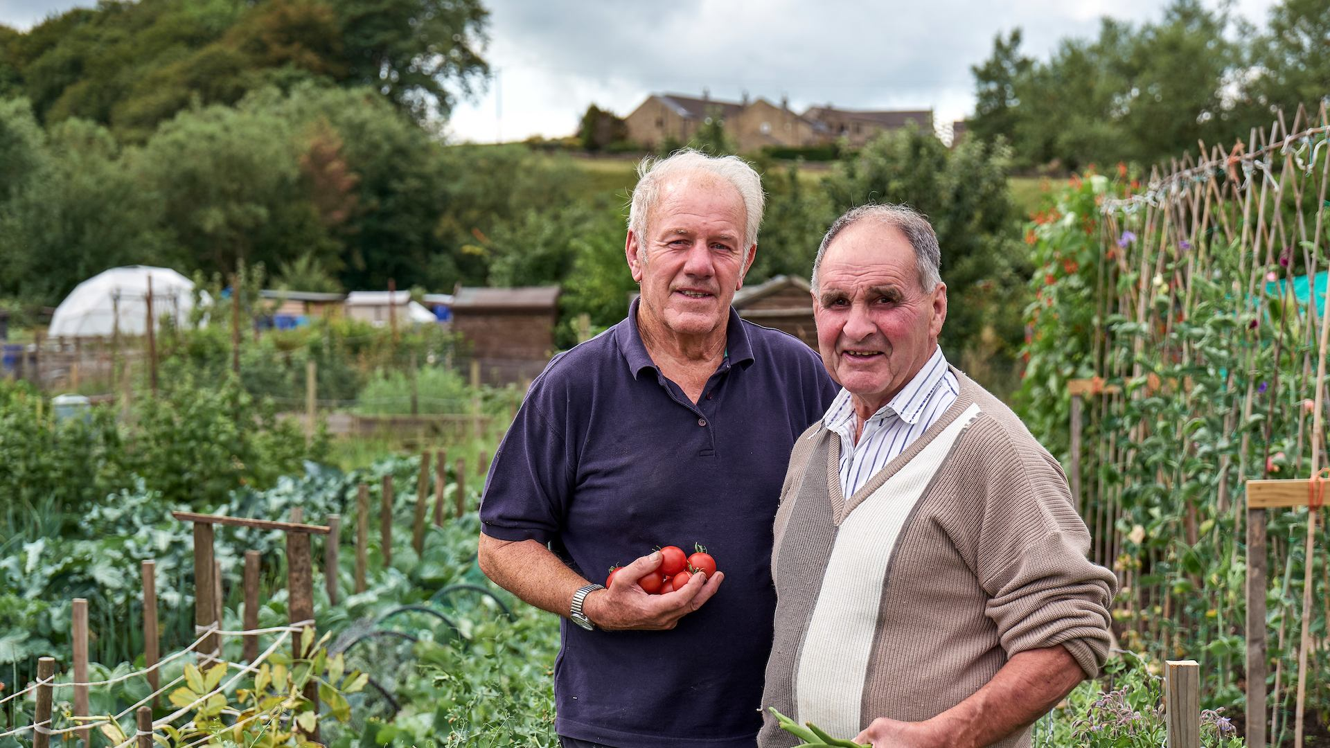two male volunteer gardeners in a community allotment