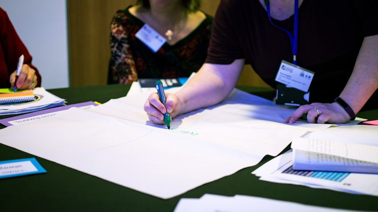 People brainstorming with pens and paper at a conference.