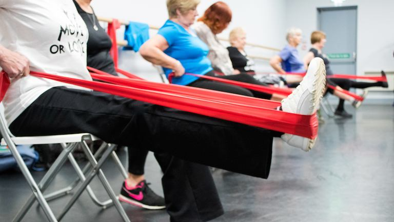 Women seated in exercise class using stretch bands on their legs.