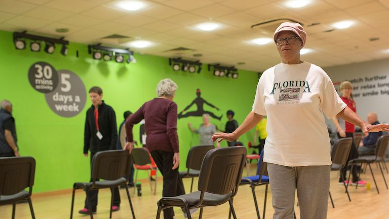 Elderly people participating in a strength and balance class.