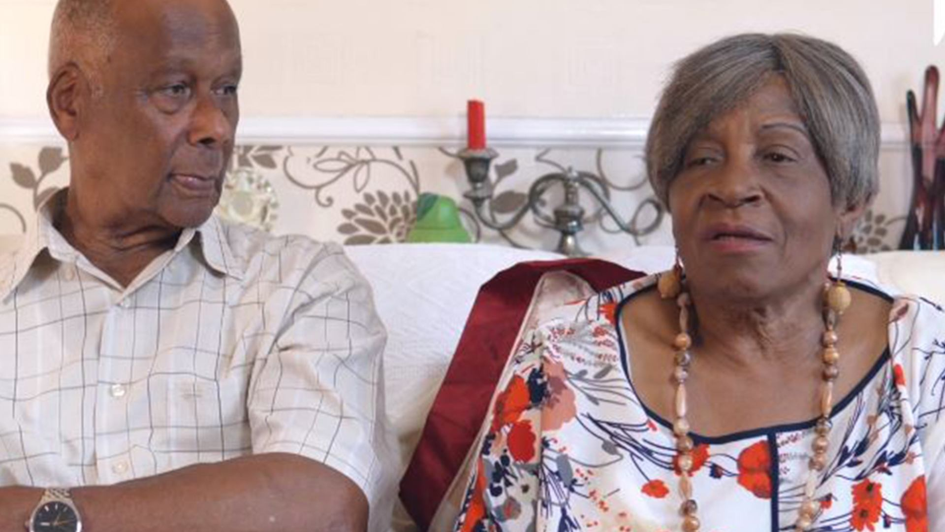 Elderly black couple sitting on sofa at home.