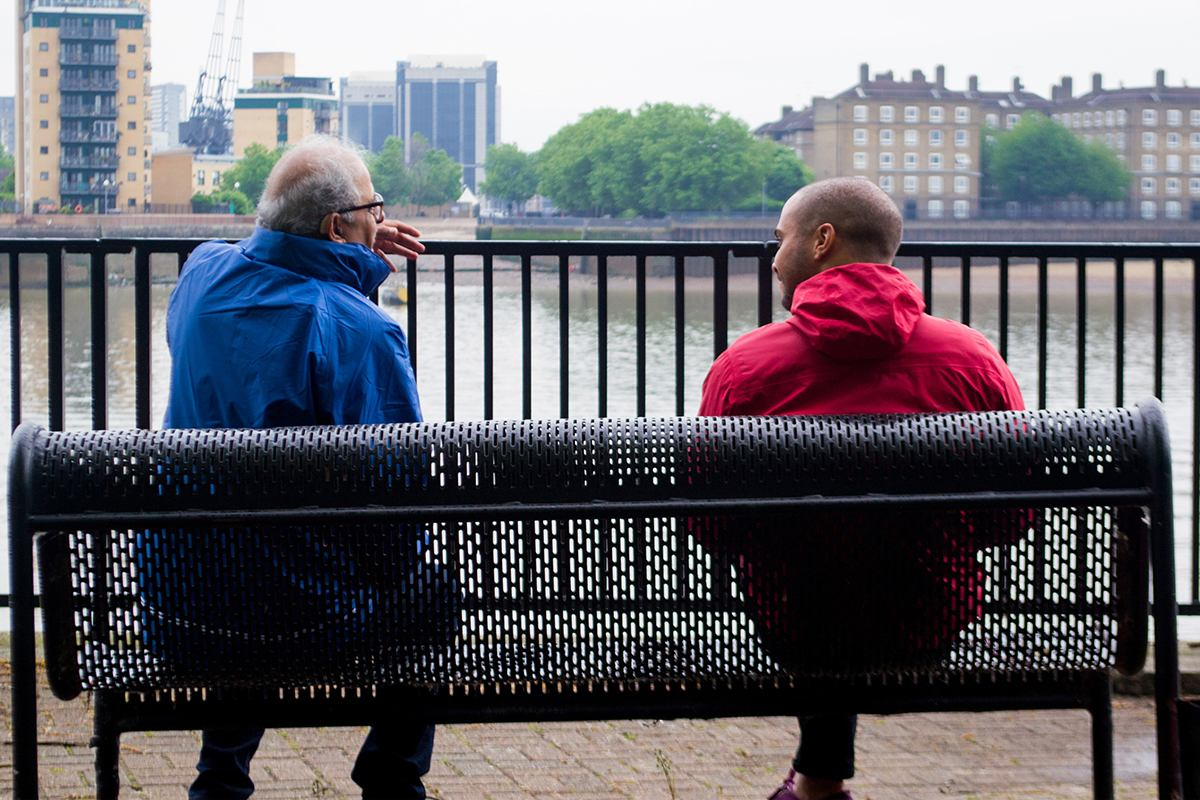 Two men seated on a bench by the Thames