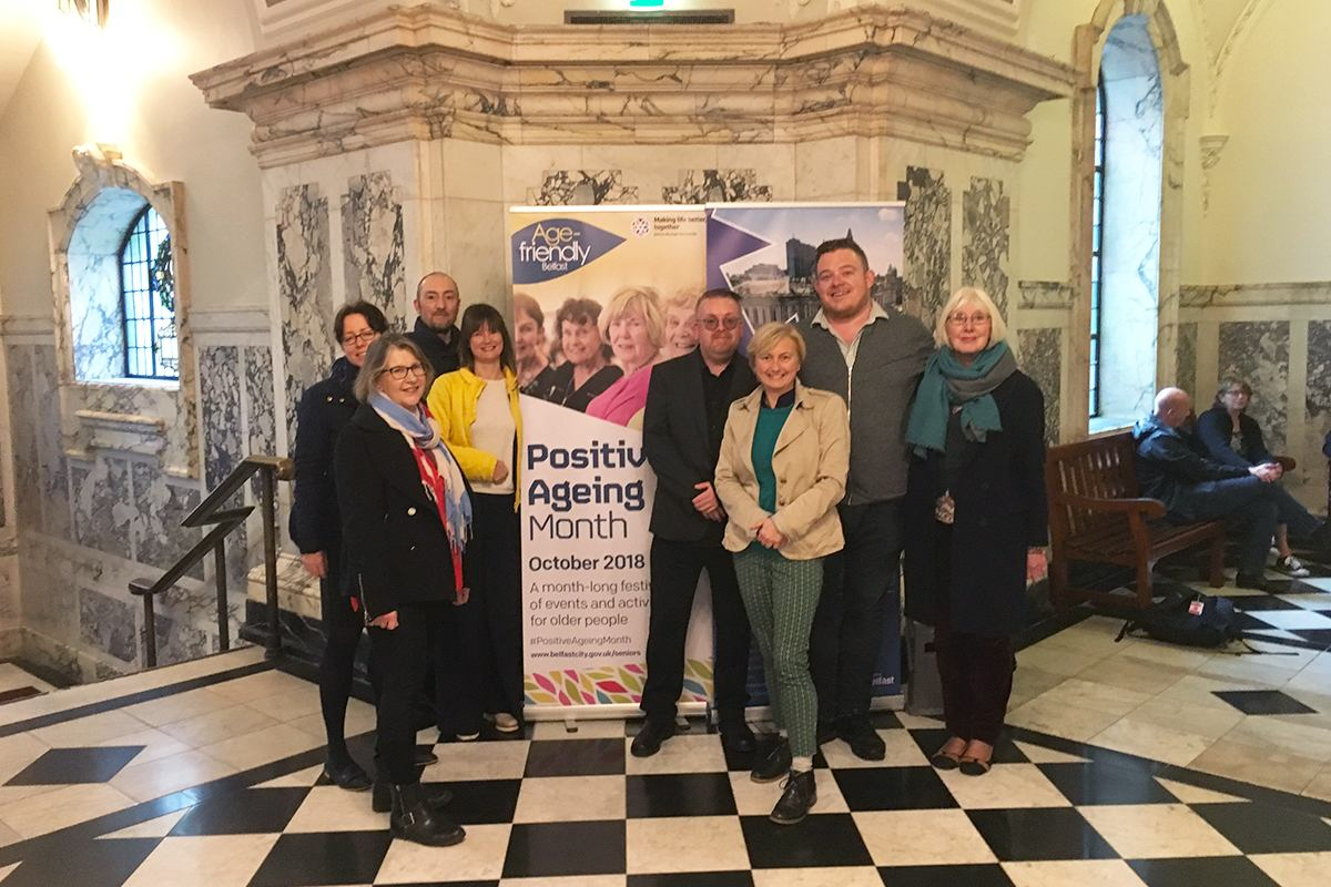 Group of people standing before a Positive Ageing Month banner.