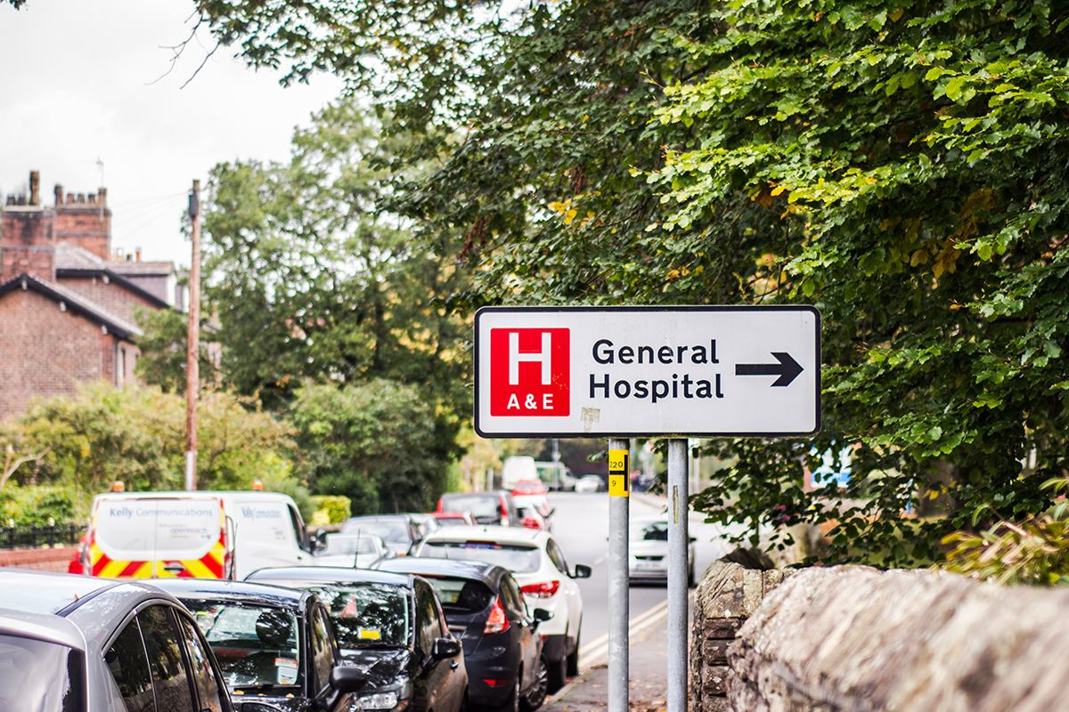 This photo is taken on the street outside of a hospital with sign saying 'General Hospital'.