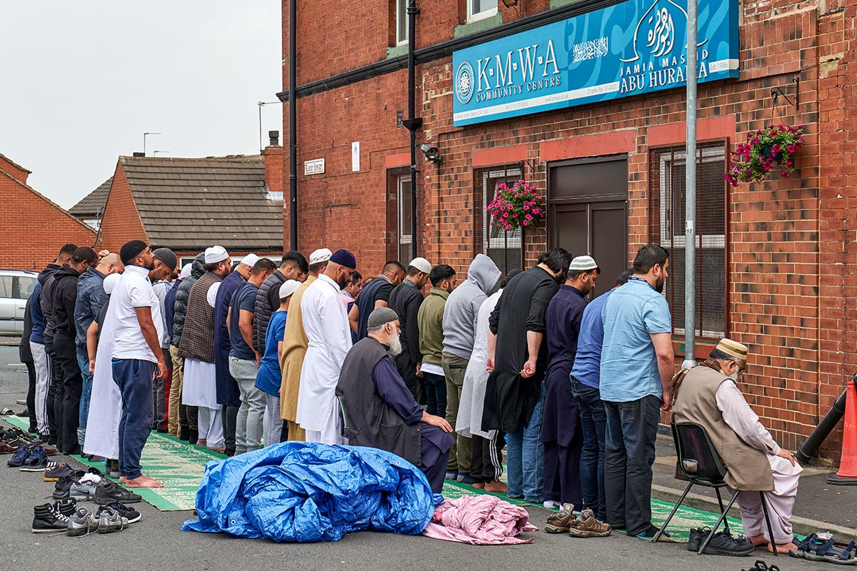 Group of muslim men prayer in front of building.