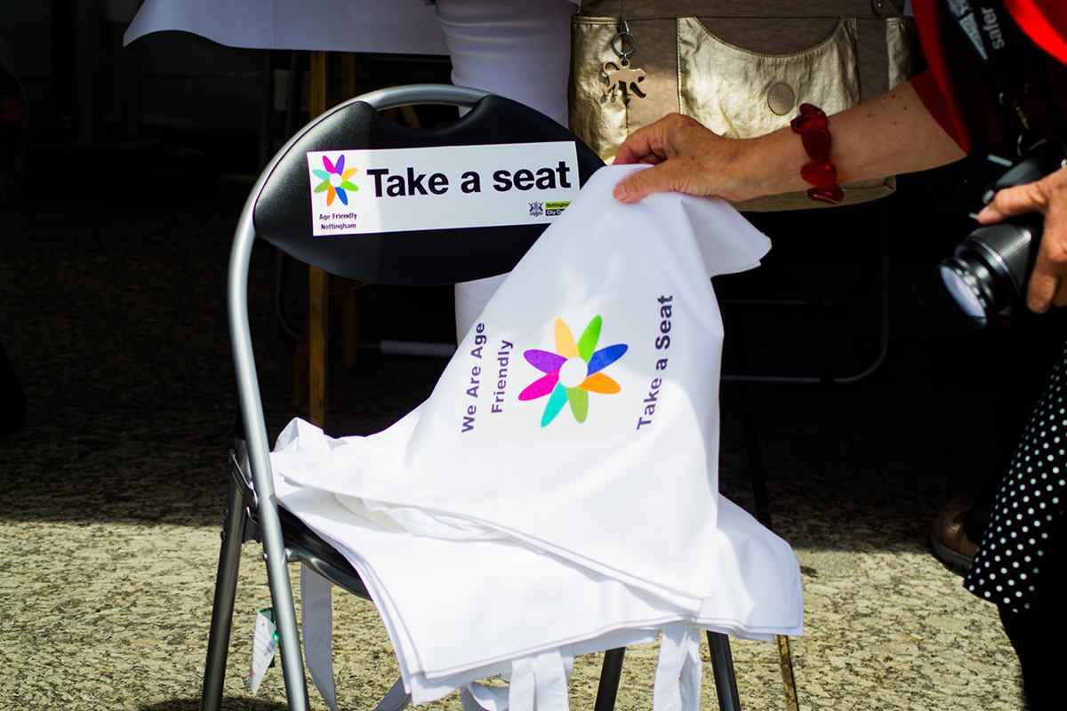 Folded chair with Take a seat campaign label and Take a seat campaign tote bags.