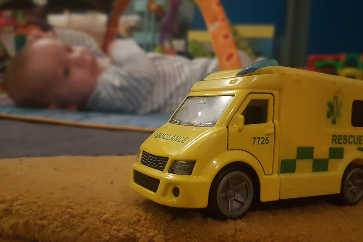 Toy ambulance in focus in foreground with a baby lying on floor in the background.