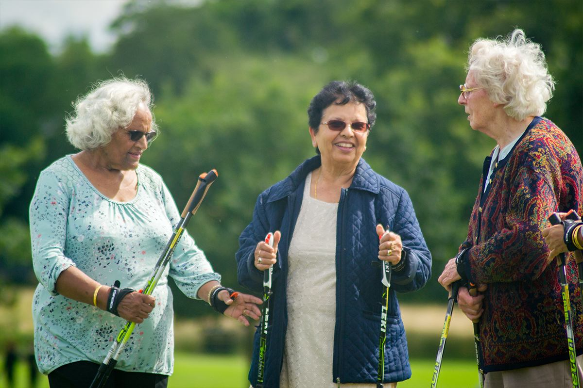 Three elderly women with nordic walking sticks.