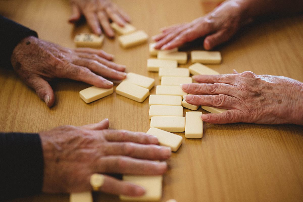 Elderly hands playing dominos.