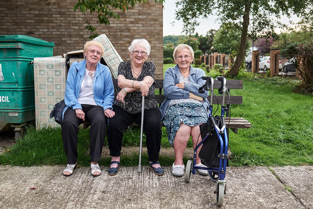 Three ladies in later life sitting on a bench