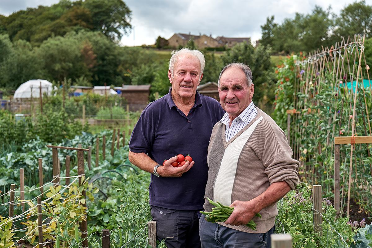 two male gardeners in a community allotment