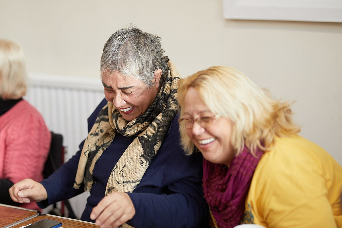 two women volunteers laughing mid-conversation