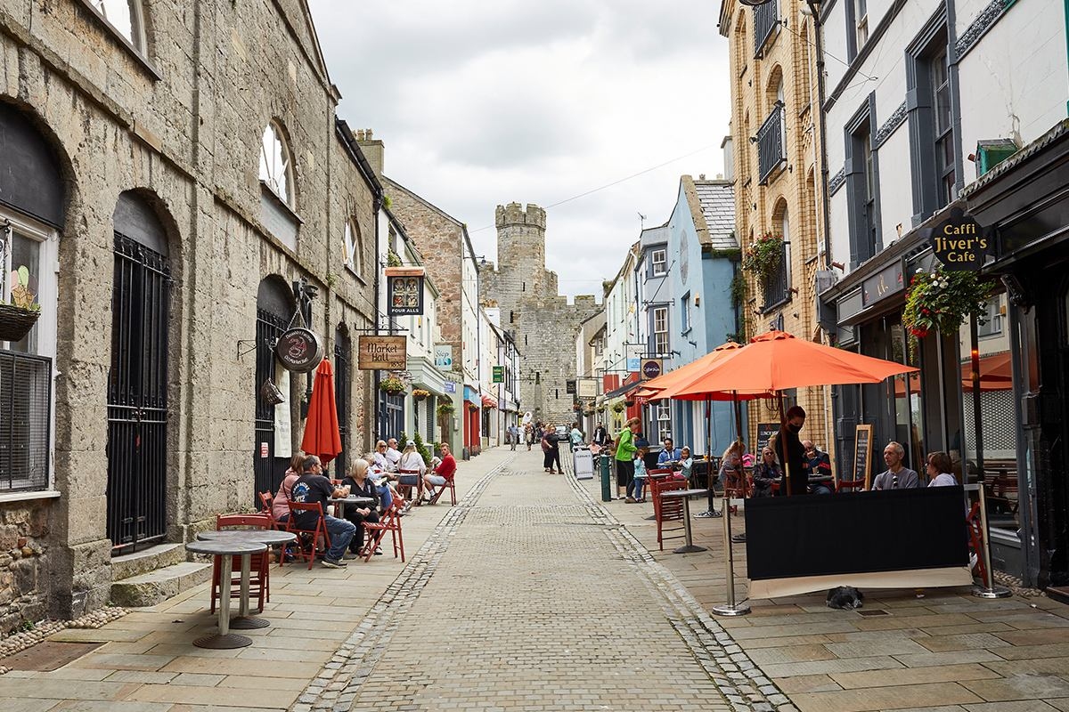 view down a paved street lined with shops and cafes with people seated outside