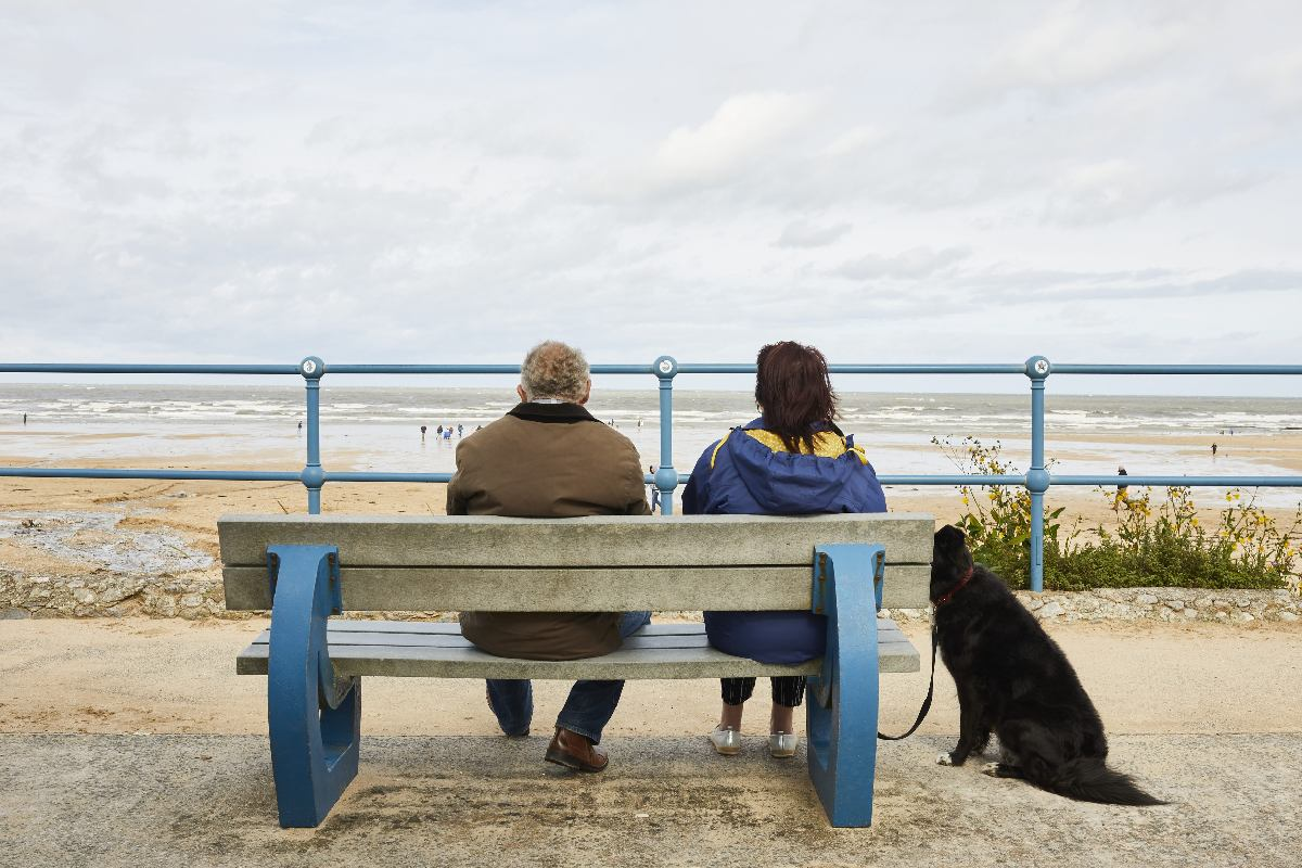 an older couple with their dog, sitting on a bench looking out to sea