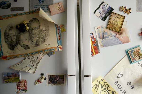 Family fridge covered in photos and magnets