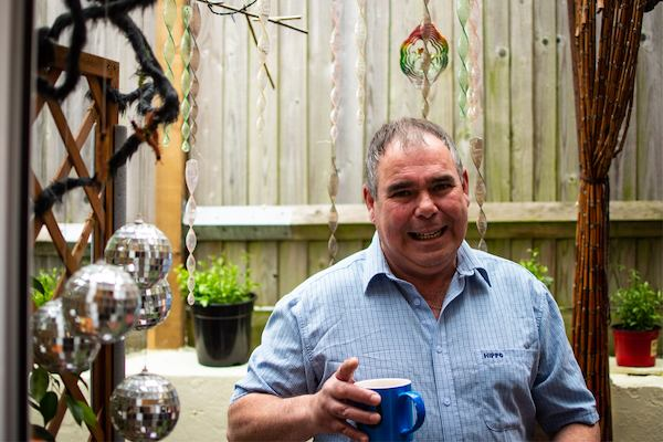 Man in a garden holding a mug of tea