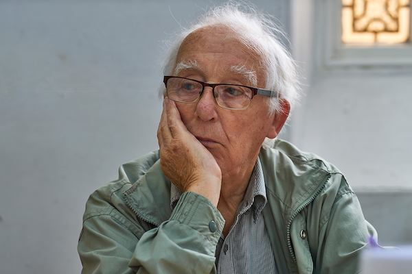 Elderly man sitting alone in thought.