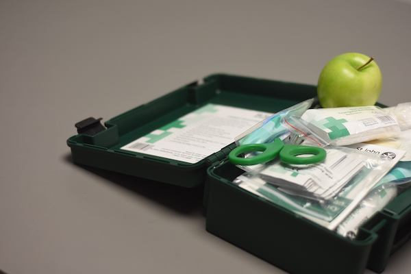 Open first aid kit with a green apple in it.