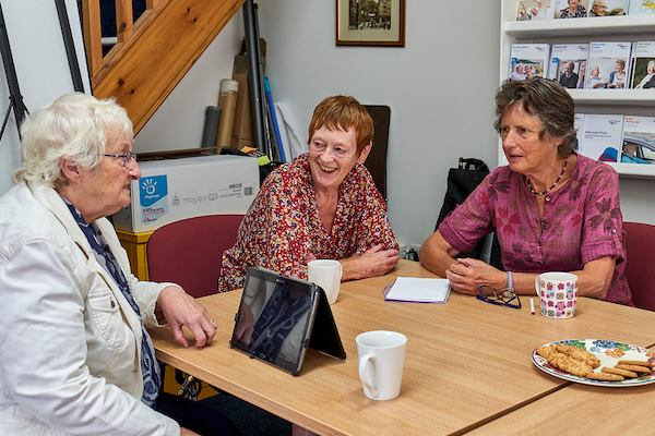 Women gathered at a table having tea and biscuits and using a tablet.