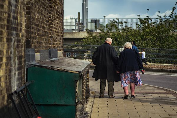 Elderly couple seen walking from behind.