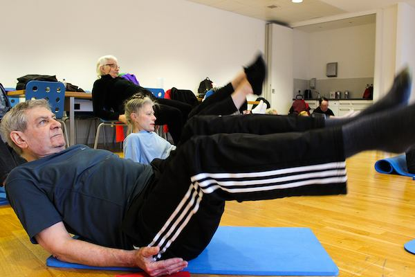 Pupils in a physio yogalates class doing a balancing rocking pose.