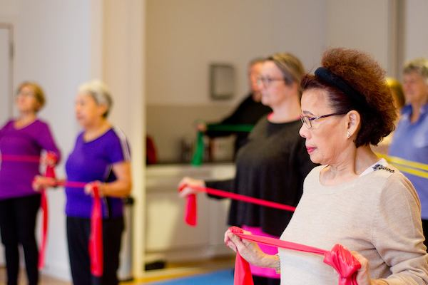 Older Asian woman using resistance band